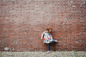 Little girl up against brick wall